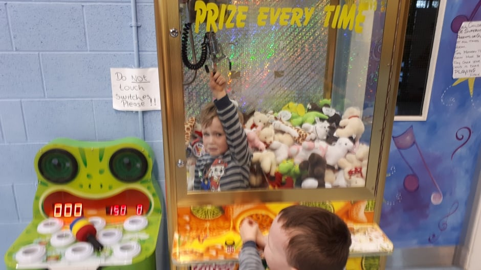 Three-year-old Jamie Murphy inside the claw prize machine with his brother, Shane, looking on.