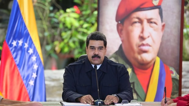 The government of Venezuelan President Nicolas Maduro, seen here sitting in front of an image of late president Hugo Chavez, contends that elections are not a priority amid more pressing matters, such as food shortages and triple-digit inflation.