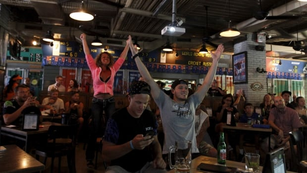 People may be less willing to pay for cable television of late, but the one thing they still want to watch live is sports, as these people watching the Super Bowl in a sports bar last year demonstrate.
