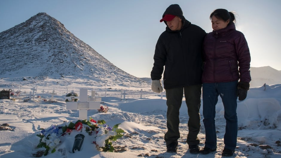 Matthew Kilabuk, left, and Geela Kooneeliusie visit their daughter Ileen's grave outside of Qikiqtarjuaq, Nunavut. The 15-year-old died of TB in January of 2017.