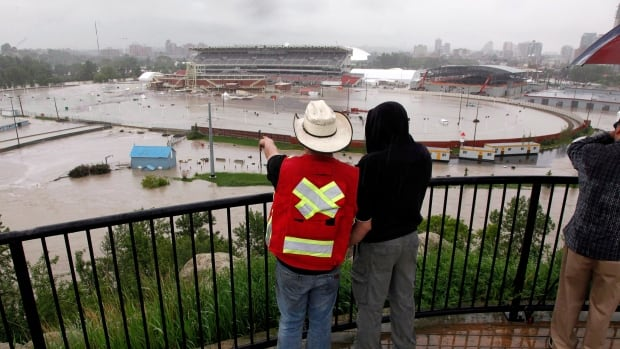 Calgarians look out over a flooded Calgary Stampede grounds and Saddledome in June 2013. The city is now looking at options to mitigate flood damage along rivers that flow within the city.