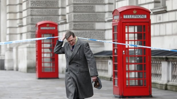 An MP ducks under police tape on Whitehall the morning after the attack.