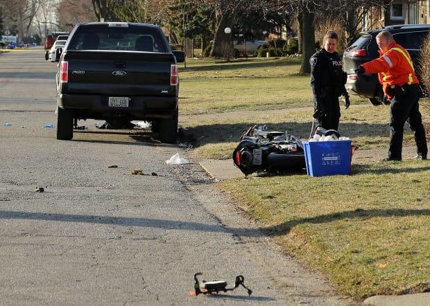 Windsor police officers on Woodlawn Avenue investigate a motorcycle collision