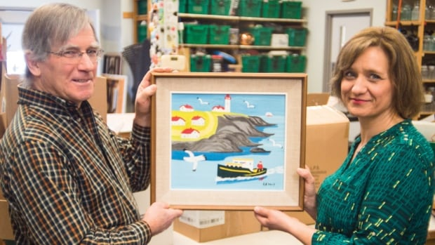 Louis Silcox, a volunteer, and Karla Richards, the general manager of the New Hamburg Thrift Centre, hold an original Maud Lewis painting discovered at centre amongst donations.