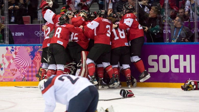 e49a06e9c0c Team USA s Michelle Picard kneels on the ice as Team Canada celebrates  their overtime win in the women s gold-medal hockey game at the Sochi  Olympics in ...