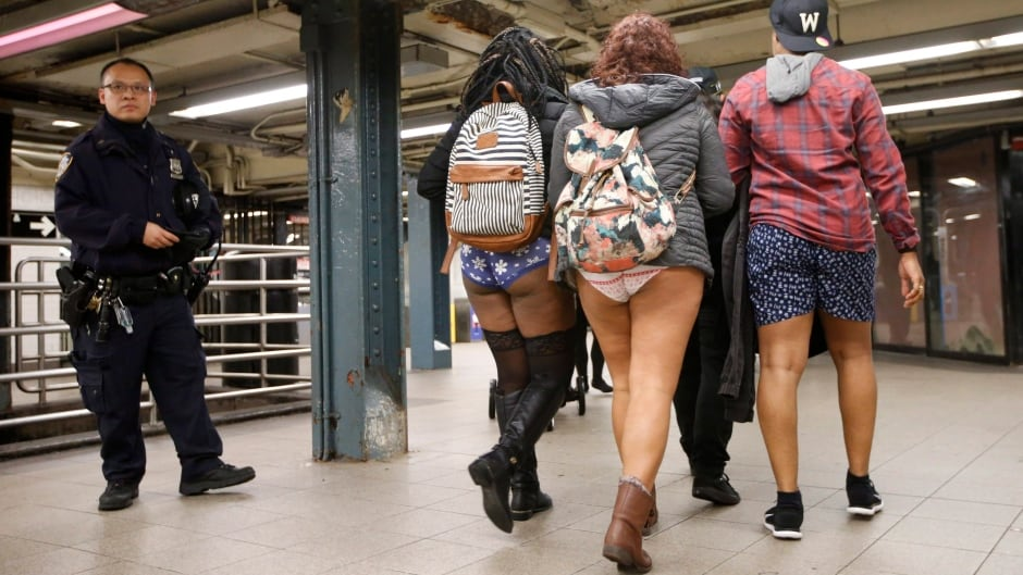 A police officer stands guard in a Manhattan subway station as three pantless people stroll by during the 15th annual No Pants Subway Ride, Sunday, Jan. 10, 2016, in New York.  The group prank, meant to amuse, has been going on since 2002. (AP Photo/Kathy Willens)