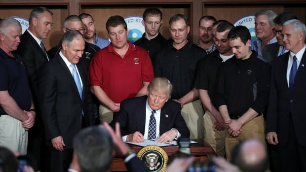 In the company of coal miners, U.S. President Donald Trump signs an executive order eliminating Obama-era climate change regulations at the Environmental Protection Agency in Washington.