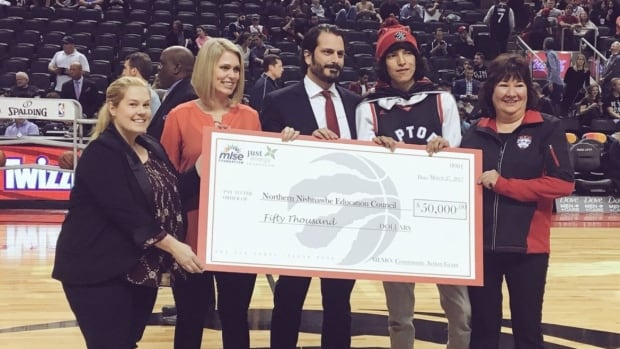 The cheque presentation for the $50,000 Toronto Raptors Community Action Grant was made at halftime at centre court. Pictured, left to right, are staff members from MLSE And Just Energy!,  with, second from right, Dennis Franklin Cromarty student Jaden Meekis of Deer Lake First Nation and, far right, Northern Nishnawbe Education Council executive director Norma Kejick.