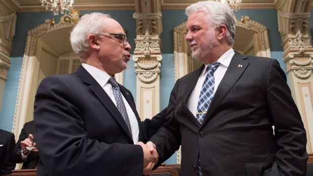 Quebec Premier Philippe Couillard, right, shakes hand with Quebec Finance Minister Carlos Leitao moments before presenting the budget speech on Tuesday.