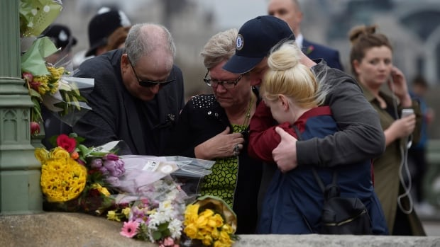 People embrace Wednesday after laying flowers during an event to mark one week since a man drove his car into pedestrians on Westminster Bridge then stabbed a police officer in London.