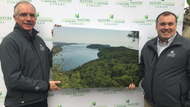 Gary Davies (left) and James Duncan, both with the Nature Conservancy of Canada hold a photo of Big Trout Bay, a 21-kilometre stretch of pristine Lake Superior shoreline, south of Thunder Bay, Ont.,  just purchased by the organization.