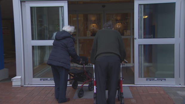 Two of the seniors who were facing eviction from Terraces on 7th, a Vancouver retirement home, re-enter the building following a press conference on Mar. 29, 2017.