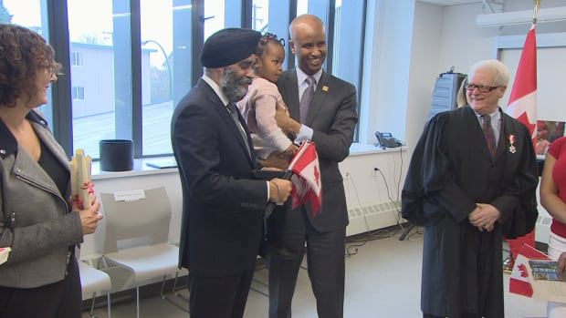 Immigration Minister Ahmed Hussen (centre) and Defence Minister Harjit Sajjan attend a citizenship ceremony in Vancouver on March 29, 2017.