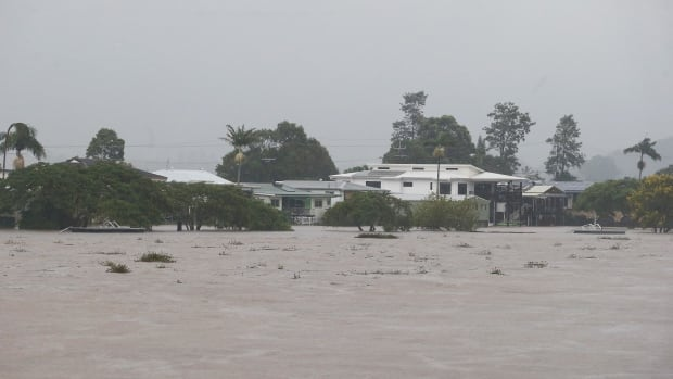 Houses are shown along the Tweed River as flood waters rise on Thursday in Murwillumbah, Australia. It is one of the towns affected by an evacuation order, as is Lismore to the south, a town of over 25,000 people.