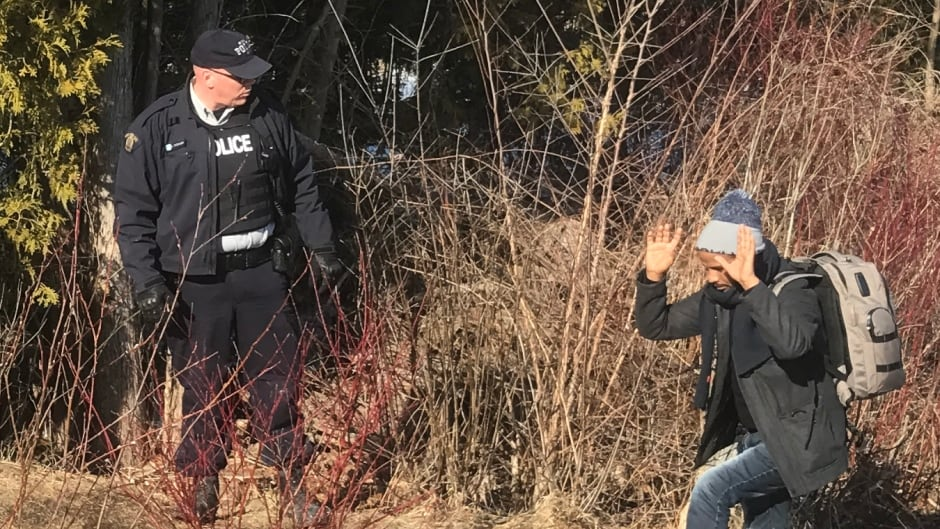 RCMP greet three men illegally entering Quebec from Roxham Road in upstate New York on Thursday.