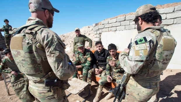 Canadian special forces soldiers, left and right, speak with Peshmerga fighters at an observation post, in northern Iraq in February of 2017. Steven Zhou said Canada needs to examine the country's military plays in an 'endless cycle of violence.'