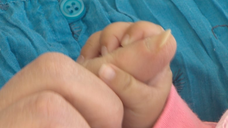 https://i.cbc.ca/1.4049594.1490972564!/fileImage/httpImage/image.jpg_gen/derivatives/original_780/barb-pike-holding-foster-baby-s-hand.jpg
