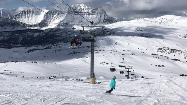 A snowboarder carves their way down the mountain at Sunshine Village this week.