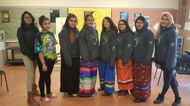 Members of Thom Collegiate's all-female drumming group pose for a photo. Brianne LaPlante (fifth from right), and Shanikwa Noname (second from right), both say the group has helped them build confidence and connect with their culture.