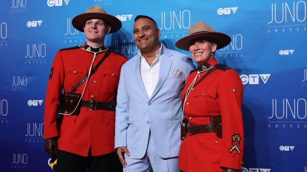 Russell Peters, co-host for the Juno Awards, poses with two Mounties as he arrives at the Canadian Tire Centre in Ottawa. He's attracted criticism from the minister of Canadian heritage for some of his comments during the broadcast.