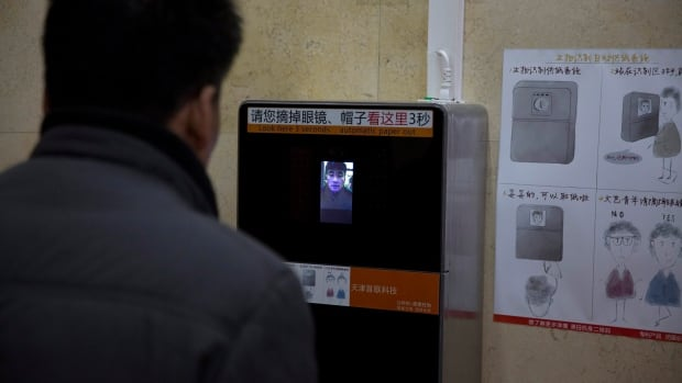 A man tries out a facial-recognition toilet paper dispenser at a toilet in the Temple of Heaven park in Beijing, China.