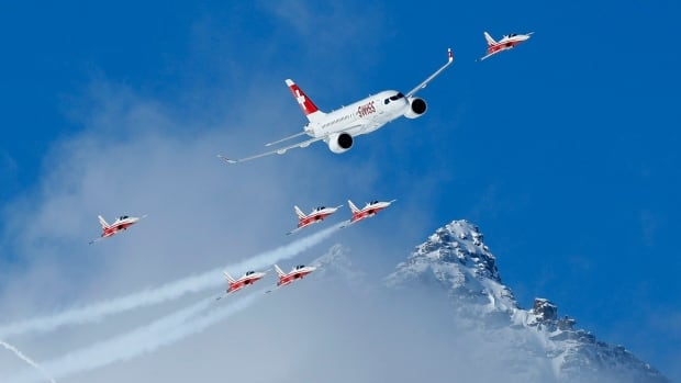 Members of the Swiss aerobatic team Patrouille Swiss fly in formation with Bombardier's CS100 earlier this year — it's enough to make Canadian taxpayers proud.