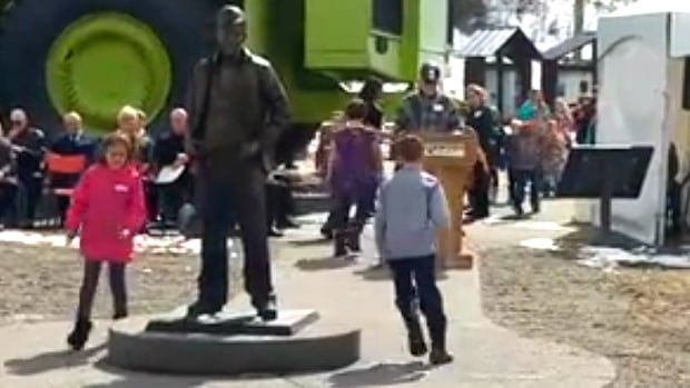 Children leave flowers at the feet of a statue dedicated to the 15 victims who died in the Balmer North mine explosion in southeast B.C. on April 3, 1967.