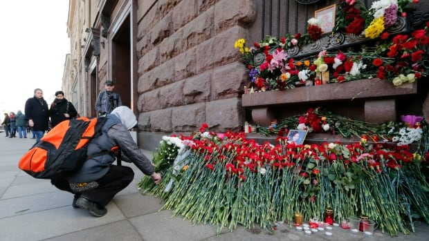 A man lays flowers outside Technology Institute subway station to pay tribute for victims of Monday's explosion in St. Petersburg, Russia. The explosion killed at least 14 people and wounded of dozens of others. An anti-terror investigation is underway.