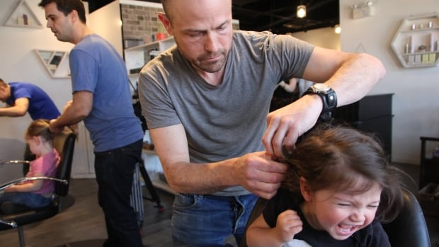 Ross Bragg styles the hair of his young daughter at a workshop in Vancouver.
