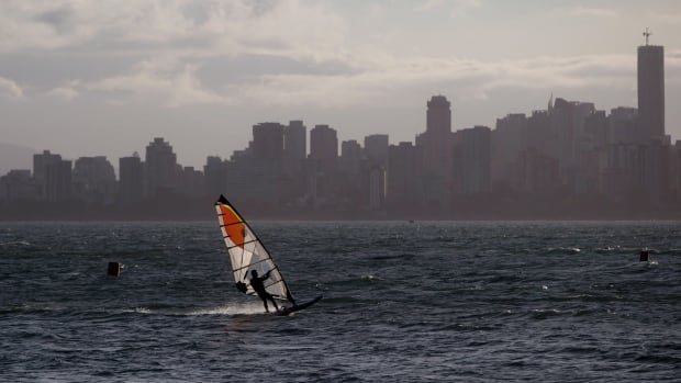 A man wind surfs on the waters off Jericho Beach in Vancouver. The Conference Board of Canada report gave Canada an overall A grade for our level of life satisfaction.