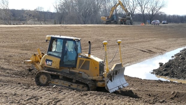 City crews in Brandon, Man., work on shoring up a dike near the Assiniboine River on Tuesday.