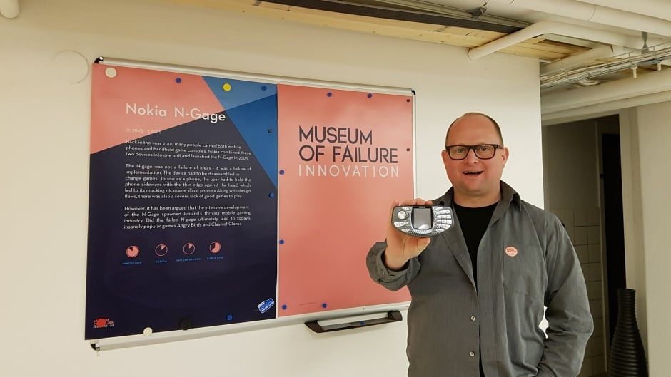 Samuel West holds up the Nokia N-Gage, a hybrid phone and gaming system from 2003 that is now part of the Museum of Failure's collection.