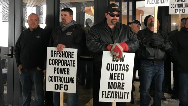 Protesters hold picket signs at DFO headquarters on White Hills Road, in response to recent cuts to shrimp quotas.