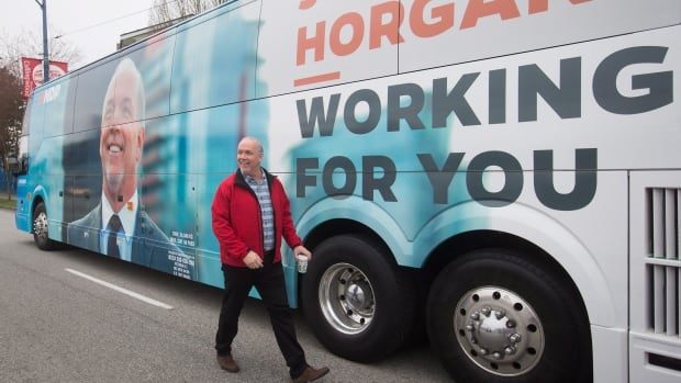 B.C. NDP Leader John Horgan walks around his election campaign bus after unveiling it in Burnaby, B.C., on Tuesday April 4, 2017. A provincial election will be held on May 9.
