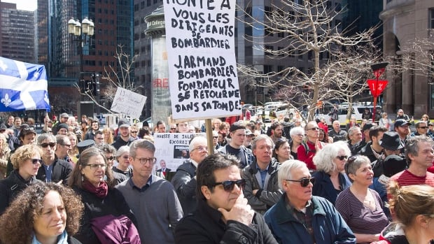 People hold up signs during a demonstration outside Quebec Premier Philippe Couillard's office on Sunday to protest recent pay hikes and bonuses to Bombardier's top executives.