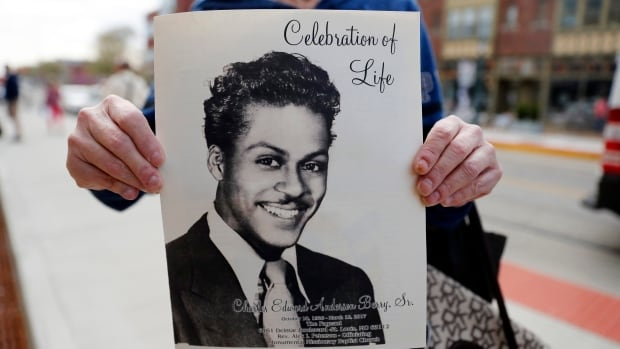 A woman holds a program outside The Pageant, a concert venue where a celebration of life is set to start for rock 'n' roll legend Chuck Berry and where Berry often performed on Sunday in St. Louis, Mo.