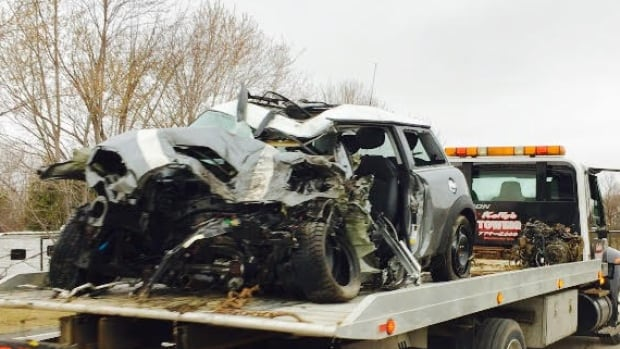 A tow truck carries the remains of the car involved in a fatal collision with a milk tanker in the Winchester Springs area on April 11, 2017.