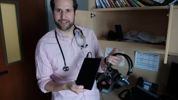 Doctor Holden Sheffield holds an iPad outfitted with the app ShoeBox, which allows doctors to easily test and diagnose hearing problems.
