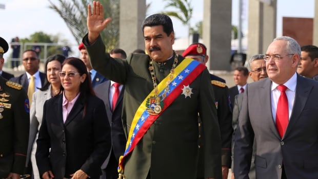 Venezuela's Nicolas Maduro, second from right, gestures as he arrives to an event to commemorate a military battle in San Felix.   Later, shouts and objects were directed at the vehicle carrying the president.