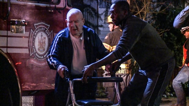 The building's manager helps one of the elderly residents with his walker, outside the building where the fire started.