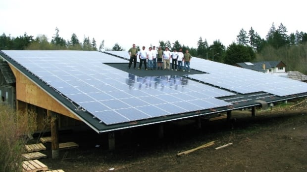 Members of the T'Sou-ke Nation gather on a massive solar panel installation, one of several powering this tiny B.C. First Nation.