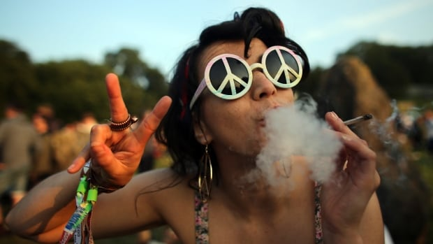 A Glastonbury reveller smokes up on the first day of the 2013 instalment of the festival in England. What happens to marijuana at music festivals when it's legalized in Canada is still a tad foggy.
