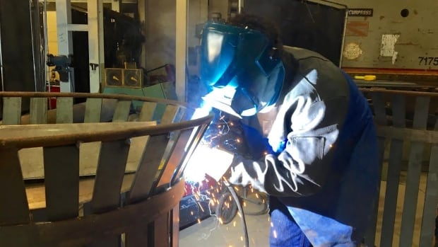 Sparks fly as first-year student Kyle Lefave welds a piece of iron into place.