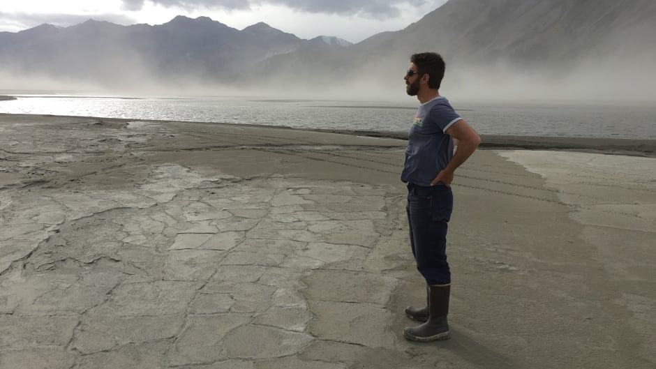 Geoscientist Dan Shugar gazes out over exposed sediments and dust storms at Kluane Lake in the Yukon in summer of 2016 - a lake covered in water just months before.