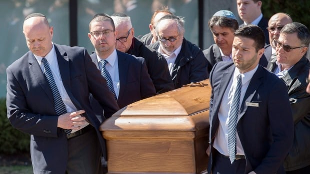 The coffin with the remains of Dr. Mark Wainberg is carried from the synagogue following his funeral.