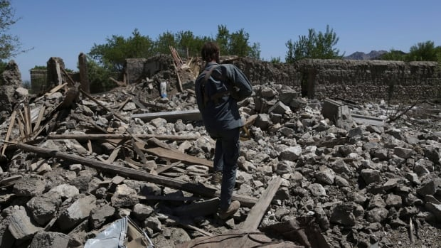 An Afghan security police walks at the destroyed house after an operation in Asad Khil near the site of a U.S. bombing in the Achin district of Jalalabad, east of Kabul.