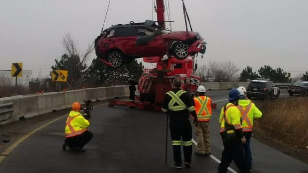 Workers remove an SUV that rolled over at Hwy 410 at Courtney Park in Mississauga  on Jan. 21, 2017 Ontario Provincial Police say the single-vehicle crash injured four people.