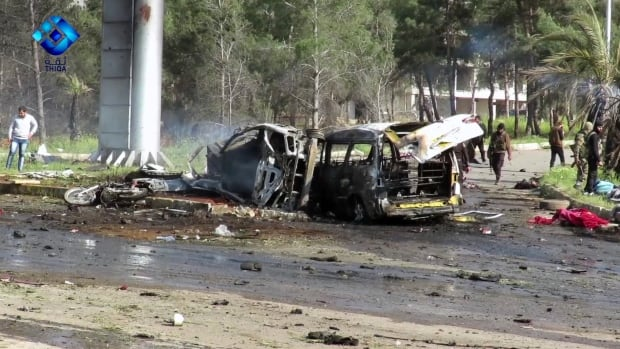 This frame grab from video provided by the Thiqa News Agency shows rebel gunmen at the site of a blast that damaged several buses and vans at the Rashideen area, a rebel-controlled district outside Aleppo, on Saturday.