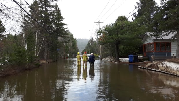 Firefighters and residents assess the flooding on Chemin de la Rivière in Val-Morin, located in the Laurentians.