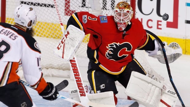 Calgary Flames goalie Brian Elliott, right, makes a save against the Anaheim Ducks' Patrick Eaves during first period of Monday's game.